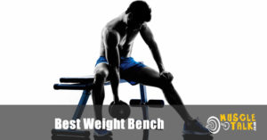 Fitness guy using dumbbells on a weight bench