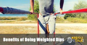 man doing weighted dips on parallel bars