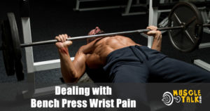 man experiencing wrist pain while bench pressing